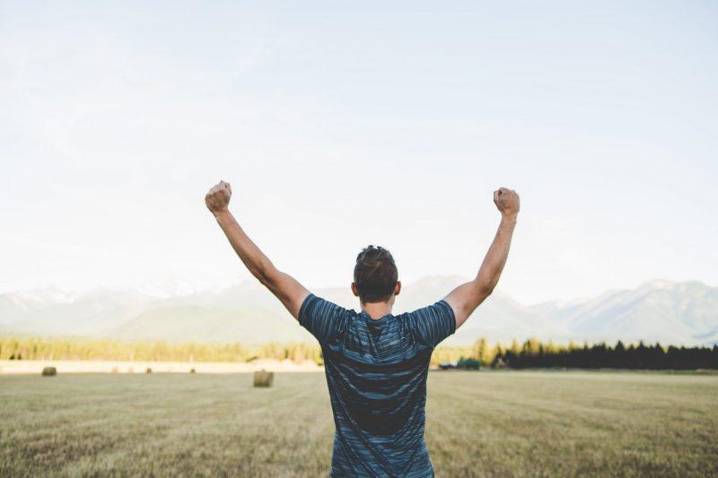 triumphant man in field