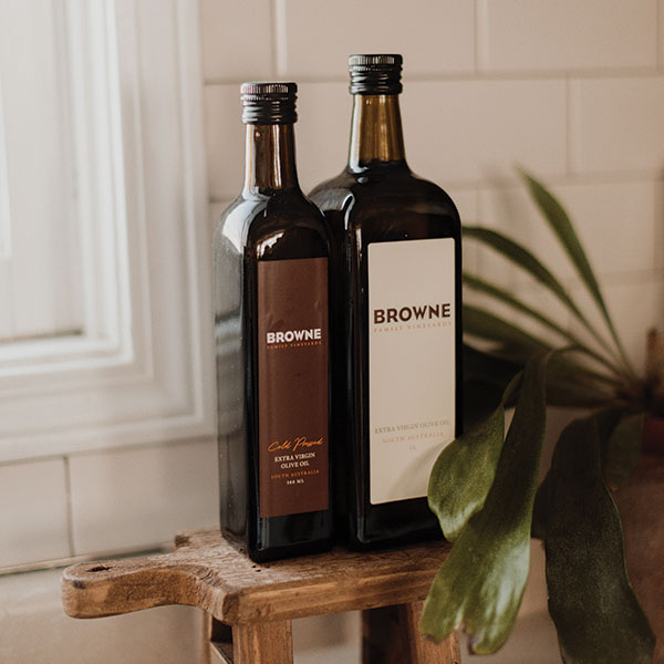 Two bottles of Browne Olive Oil sitting on a wooden cutting board