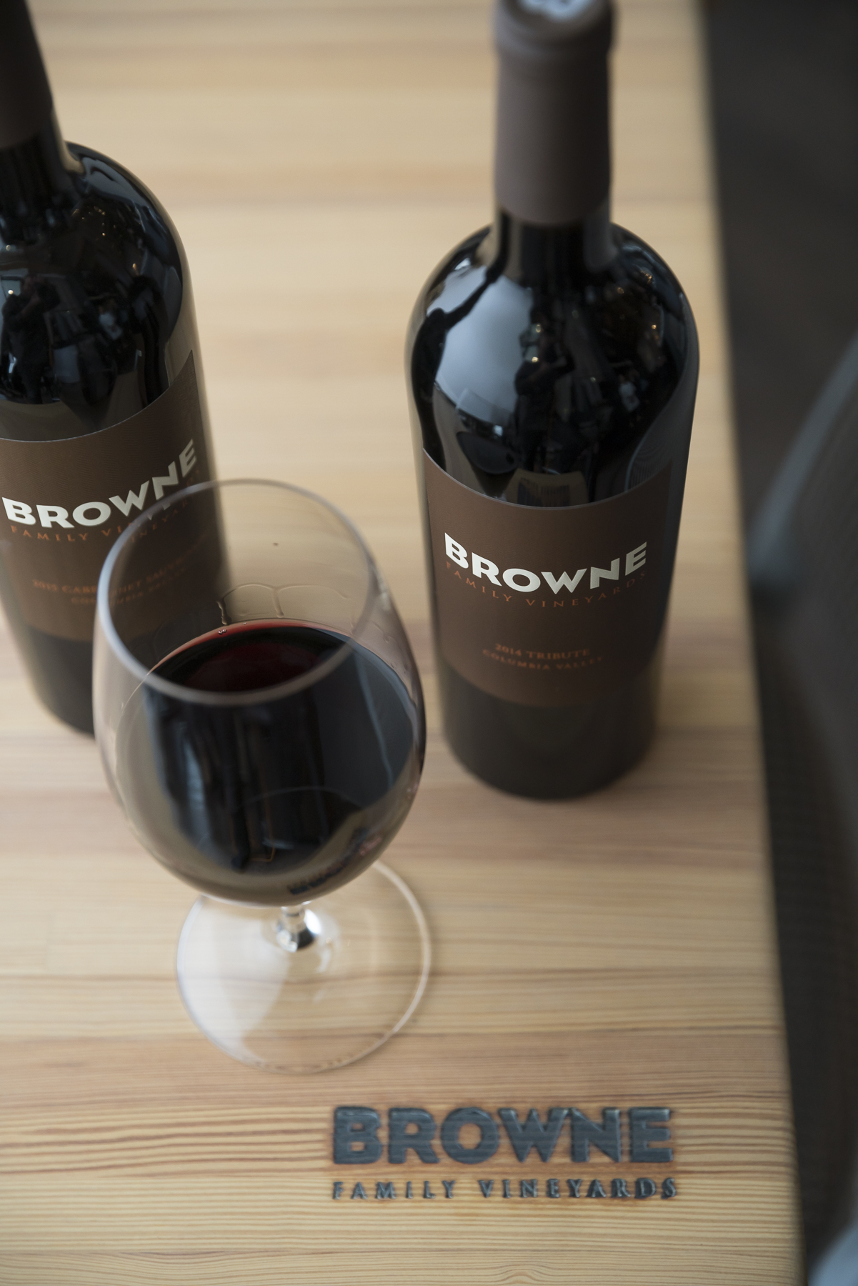 Browne wine bottle, wine glass and Browne Family cutting board